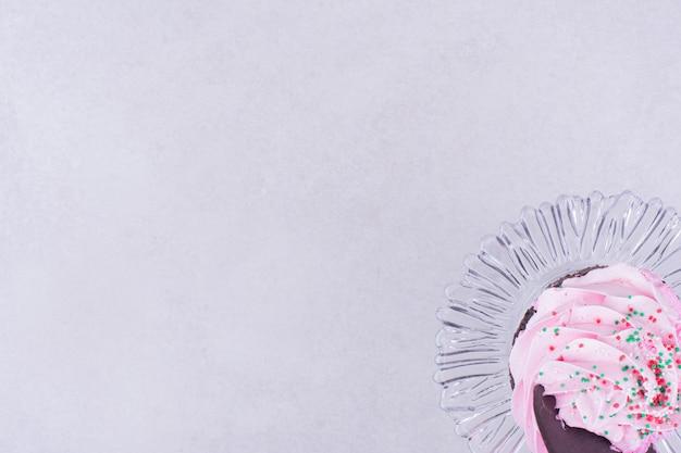Czekoladowe ciastko z różowym kremem na wierzchu.