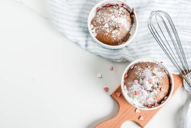 Czekoladowe ciasto lub brownie z walentynką z cukrem pudrem i posypką w kształcie serca
