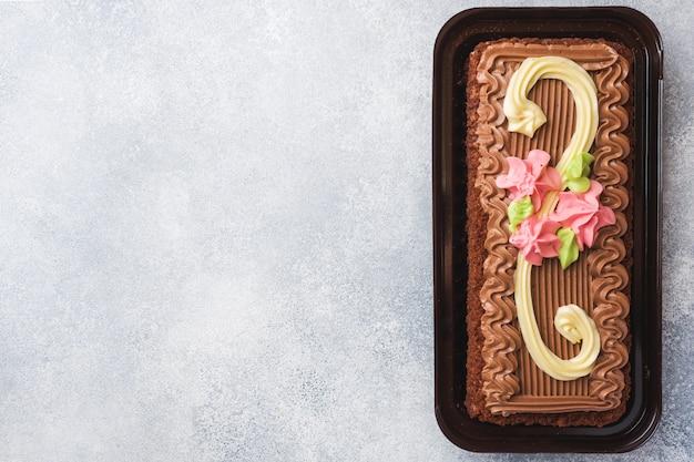 Czekoladowe ciasto prostokątne ozdobione kremowymi różami