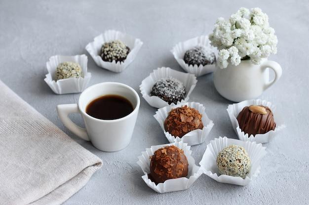 Czekoladowe cukierki, filiżanka kawy i bukiet kwiatów na walentynki na szarym stole.