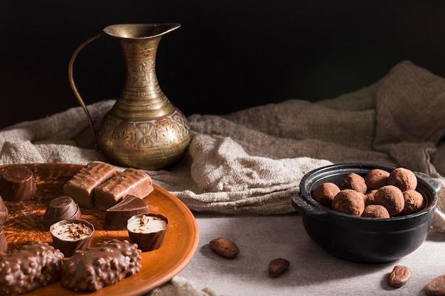 Czekoladowe cukierki pod dużym kątem na talerzu i cukierki czekoladowe w misce