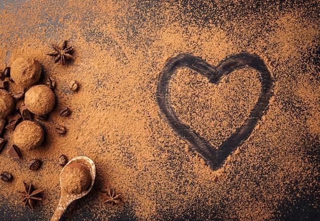 Czekoladowe cukierki truflowe z proszkiem kakaowym. domowe kulki świeżej energii z czekoladą. różne trufle dla smakoszy wykonane przez czekoladę. kawałki czekolady i ziaren kawy, malowane serce
