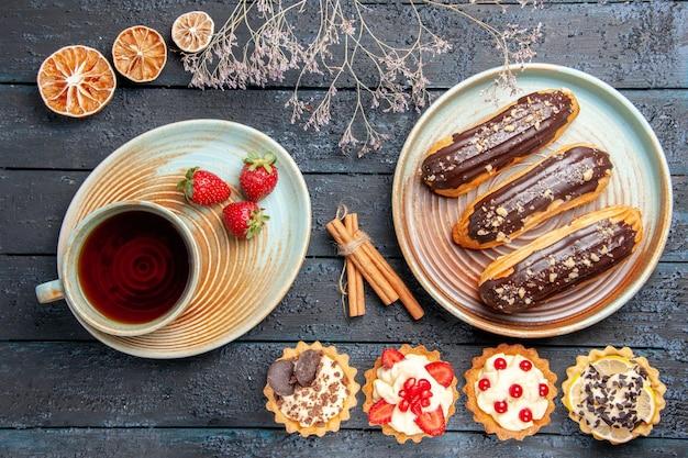 Czekoladowe eklery z widokiem z góry na owalnym talerzu tarty z suszonymi pomarańczami cynamonowymi oraz filiżanka herbaty i truskawek na spodeczku na ciemnym drewnianym stole