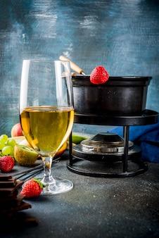 Czekoladowe fondue w tradycyjnym garnku do fondue, z widelcami, białym winem, różnorodnymi jagodami i owocami