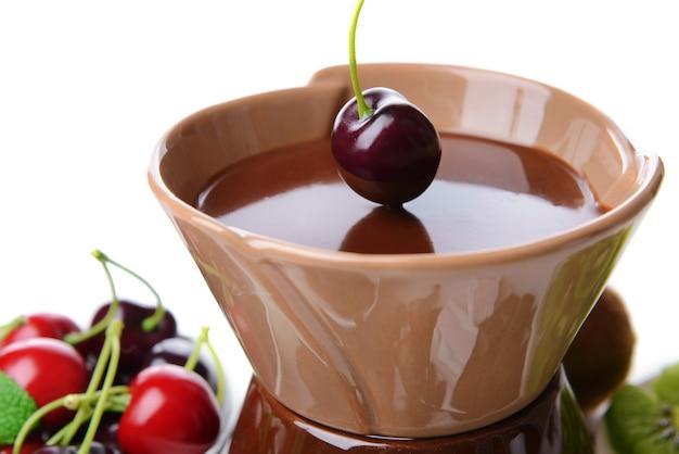 Czekoladowe fondue z pokrojonymi owocami, na białym tle