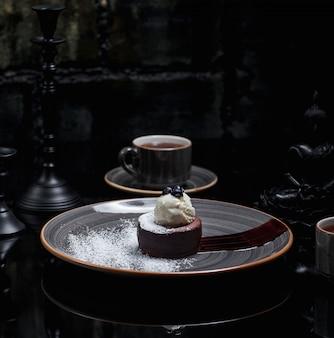 Czekoladowe fondue z pyłem cukrowym i lodami waniliowymi. obraz