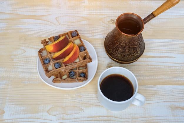 Czekoladowe gofry z owocami i filiżanką kawy