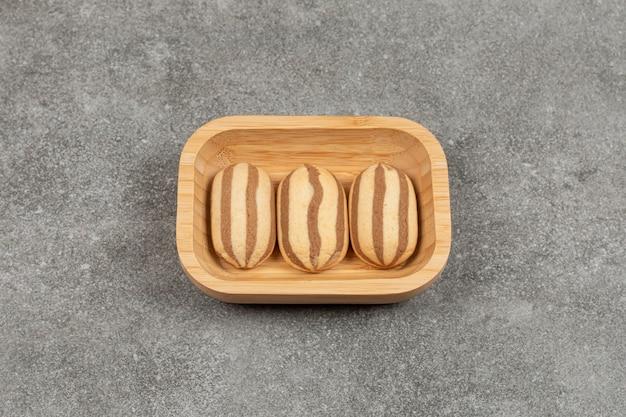 Czekoladowe herbatniki w paski na drewnianym talerzu