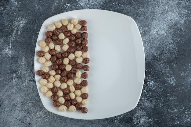 Czekoladowe i pszenne kulki na białym talerzu.