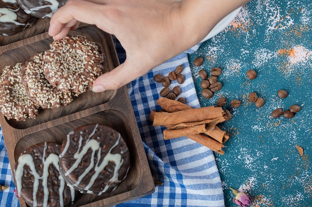 Czekoladowe i sezamowe ciasteczka na drewnianym talerzu.