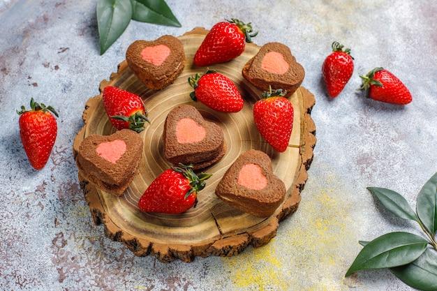 Czekoladowe i truskawkowe ciasteczka ze świeżymi truskawkami w kształcie serca, widok z góry