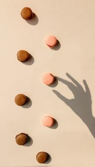 Czekoladowe i truskawkowe makrony i cień kobiecej dłoni na szarej powierzchni