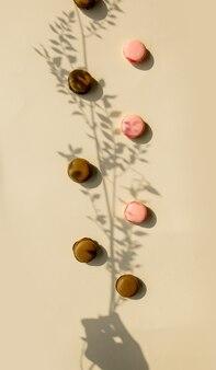 Czekoladowe i truskawkowe makrony i sucha gałąź kwiatu na żółtej powierzchni