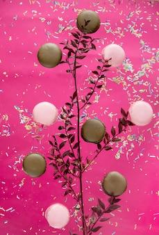 Czekoladowe i truskawkowe makrony oraz sucha gałąź kwiatu na różowej powierzchni