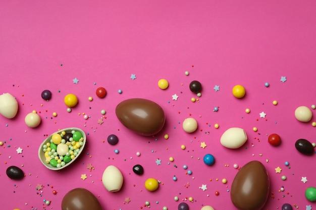 Czekoladowe jajka wielkanocne, cukierki i posypka na różowej powierzchni