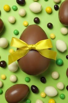 Czekoladowe jajka wielkanocne i cukierki na zielonej powierzchni