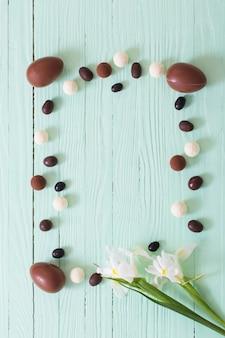 Czekoladowe jajka wielkanocne i kwiaty na zielonej powierzchni drewnianych