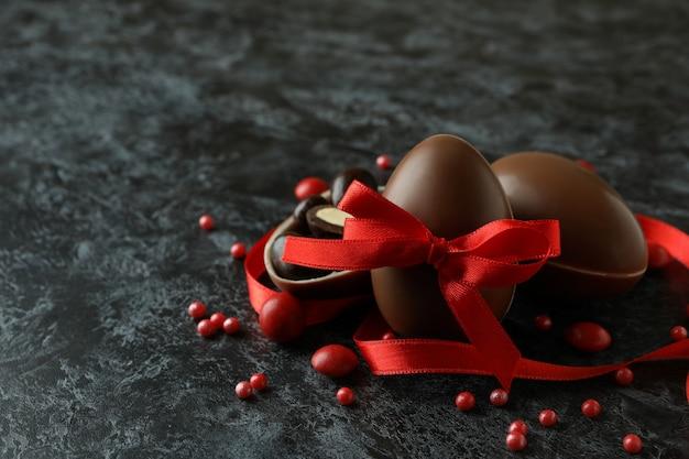 Czekoladowe jajka wielkanocne z cukierkami na czarnej zadymionej powierzchni
