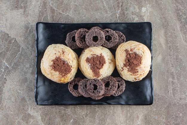 Czekoladowe krążki kukurydziane i kakao w proszku na kruchym talerzu na marmurze.