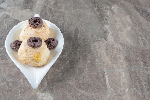 Czekoladowe krążki kukurydziane i kruche ciasto na talerzu na marmurze.