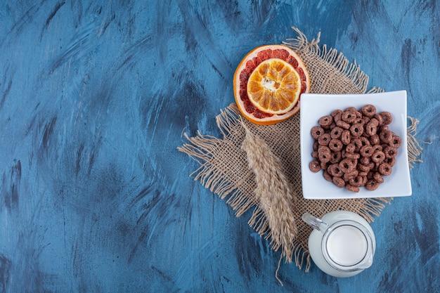 Czekoladowe krążki zbożowe na białym talerzu z suszonymi owocami i szklany dzbanek mleka.
