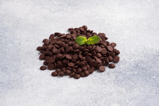 Czekoladowe krople na szarej betonowej powierzchni. kawałki czekolady do dekoracji deserów.