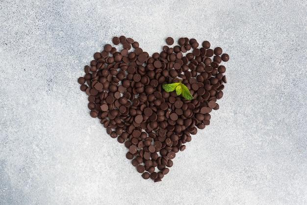 Czekoladowe krople ułożone w kształcie serca na szarej betonowej powierzchni. kawałki czekolady do dekoracji deserów.