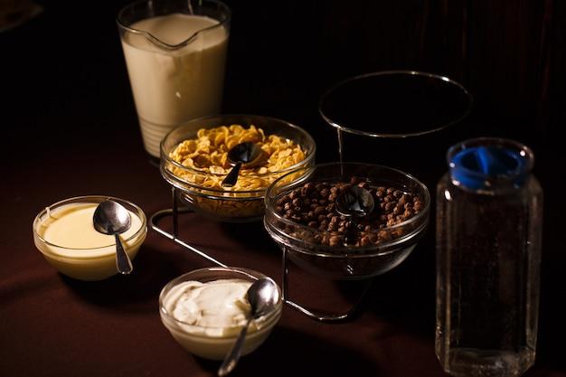 Czekoladowe kulki w misce i płatki kukurydziane z dzbankiem mleka i wody na stole oraz miską śmietany i mleka skondensowanego. pyszne i zdrowe śniadanie