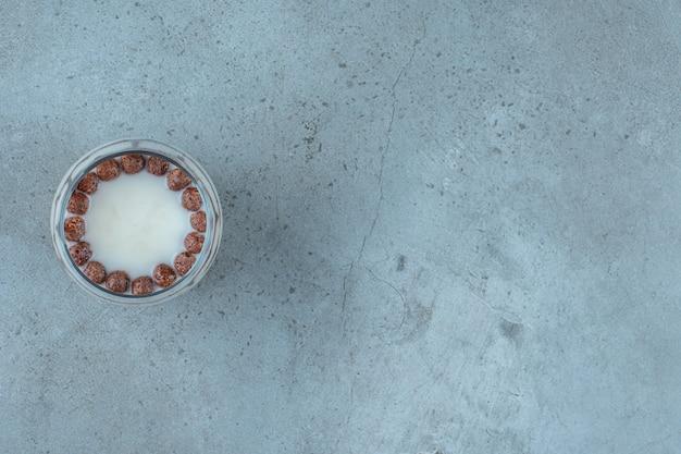 Czekoladowe kulki w szklance mleka, na niebieskim tle.