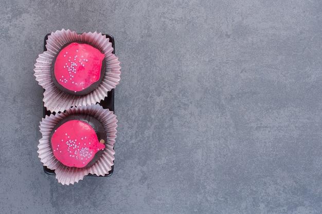 Czekoladowe kulki z różową polewą na ciemnym talerzu.