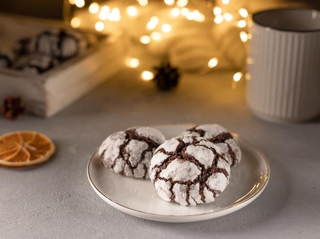 Czekoladowe marszczone ciasteczka na białym talerzu na tle rozmytych lampek choinkowych święta bożego narodzenia