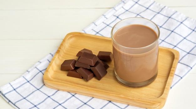 Czekoladowe mleko na białym drewnianym stole.