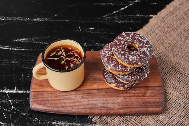Czekoladowe pączki na drewnianym talerzu z herbatą.