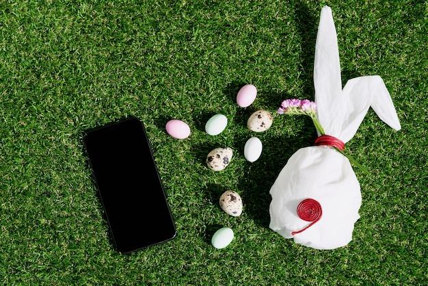 Czekoladowe pisanki w pastelowej kolorystyce i jaja przepiórcze na zielonej trawie. biały papier do pieczenia w kształcie króliczka. czarny telefon komórkowy. koncepcja wesołych świąt. skopiuj miejsce. widok z góry
