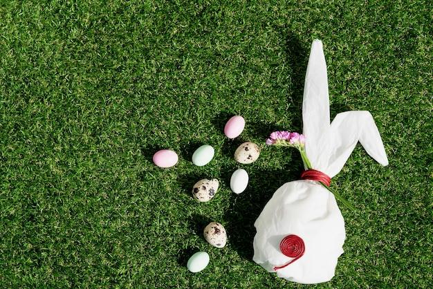 Czekoladowe pisanki w pastelowej kolorystyce i jaja przepiórcze na zielonej trawie. biały papier do pieczenia w kształcie króliczka. koncepcja wesołych świąt. skopiuj miejsce. widok z góry
