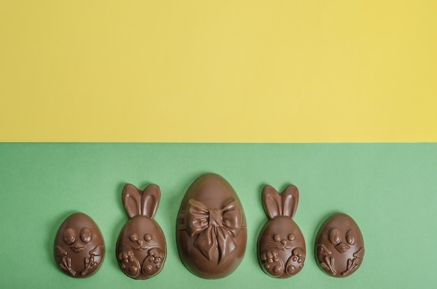 Czekoladowe pisanki w postaci królika i kurczaka na żółto-zielonym tle z miejsca na kopię.