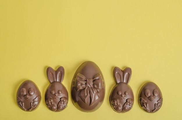 Czekoladowe pisanki w postaci królika i kurczaka na żółtym tle z miejsca na kopię.
