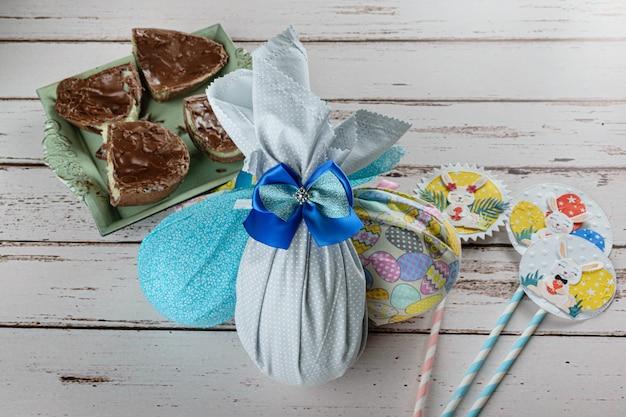Czekoladowe pisanki zapakowane w kolorowe tkaniny. obok pisanka faszerowana białym brigadeiro (brygadier).