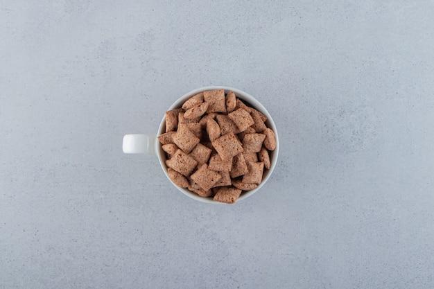 Czekoladowe płatki kukurydziane w ceramicznym kubku na kamiennej powierzchni