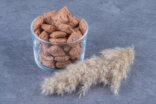 Czekoladowe płatki kukurydziane w szklance obok trawy pampasowej, na niebieskim stole.