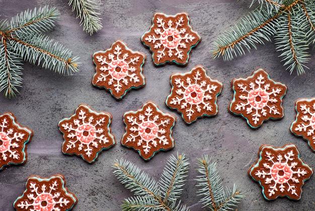 Czekoladowe płatki śniegu z kolorowym lukrem na ciemnym tle z jodłowymi gałązkami