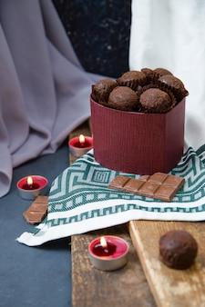 Czekoladowe pudełko i płonące świeczki na drewnie