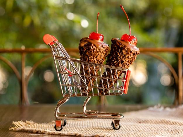 Czekoladowe rożki lodów z wisienką na wierzchu na koszyku na rustykalnym drewnianym tle