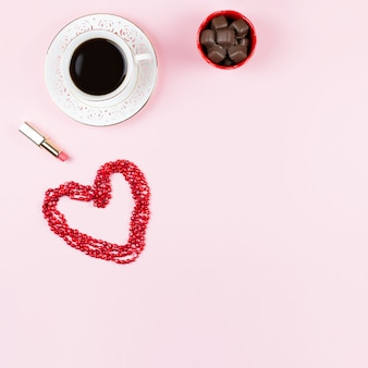 Czekoladowe słodycze, czarna kawa, szminka. kobiecy tło w kolorach czerwonym i białym.