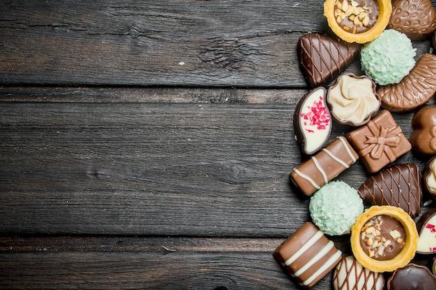 Czekoladowe słodycze z orzechami i różnymi nadzieniami na drewnianym stole.