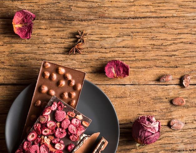 Czekoladowe tabliczki płasko ułożone z orzeszkami ziemnymi i suszonymi owocami