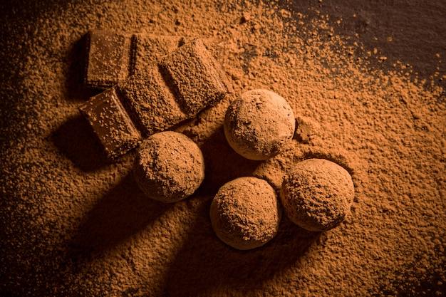 Czekoladowe trufle, truflowe cukierki czekoladowe z proszkiem kakaowym. domowe kulki świeżej energii z czekoladą. gourmet różne trufle wykonane przez chocolatier. kawałki czekolady