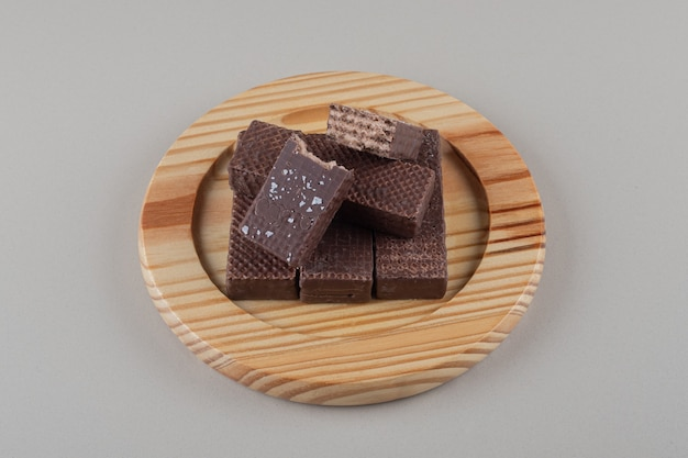 Czekoladowe wafle spakowane razem na drewnianym talerzu na marmurowym tle.