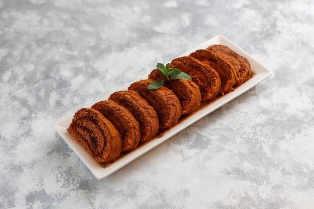 Czekoladowego torta rolka z kakaowym proszkiem na bielu talerzu, odgórny widok