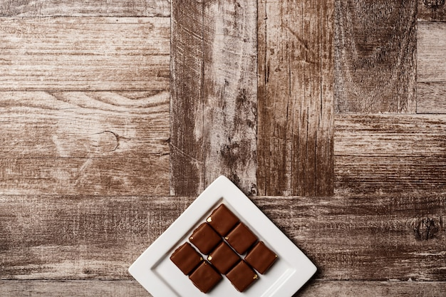 Czekoladowi cukierki na bielu talerzu na drewnianym